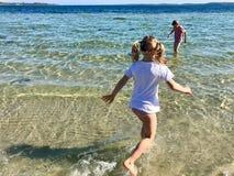 Gioco felice dei bambini allegro su una spiaggia in mare immagini stock libere da diritti