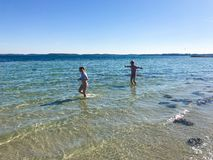 Gioco felice dei bambini allegro su una spiaggia in mare immagine stock libera da diritti