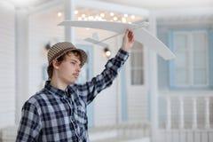 Gioco felice del ragazzo con l'aeroplano a disposizione, Immagine Stock