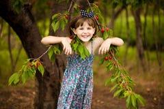Gioco felice della bambina vicino al ciliegio nel giardino di estate Ciliegia di raccolto del bambino sull'azienda agricola della immagine stock libera da diritti