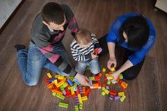Gioco felice della famiglia con i cubi Fotografia Stock