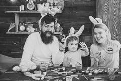 Gioco felice della famiglia Pasqua Bunny Costume Madre, padre e bambino dipingenti le uova di Pasqua Fotografia Stock