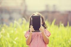 Gioco felice della ragazza all'aperto con la compressa Fotografia Stock