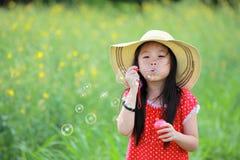 Gioco felice della ragazza con le bolle di sapone Fotografia Stock