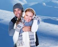 Gioco felice delle coppie all'aperto alle montagne di inverno Immagine Stock