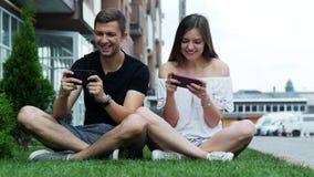 Gioco felice ed attraente del gioco delle coppie sul telefono cellulare L'uomo e la donna caucasici passano il tempo libero video d archivio
