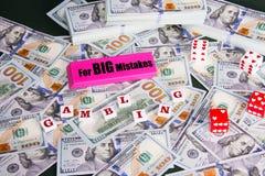 Gioco: Gomma rosa con il messaggio realmente grande di errori, i dadi ed i dollari americani sparsi ed impilati Immagini Stock Libere da Diritti