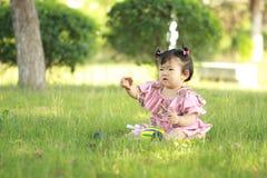 Gioco innocente della neonata una palla sul prato inglese Fotografie Stock Libere da Diritti