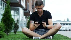 Gioco mobile del gioco felice dell'uomo sullo smartphone, sedentesi sull'erba vicino alla casa archivi video