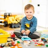 Gioco sorridente del ragazzo con i suoi giocattoli colorati Fotografie Stock