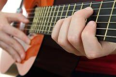 Gioco su una chitarra acustica Fotografie Stock Libere da Diritti