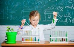Gioco sveglio dell'allievo della scuola della ragazza con le provette ed i liquidi variopinti Esperimento chimico della scuola Is immagini stock
