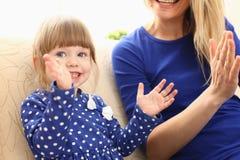 Gioco sveglio della bambina con il picchiettio-un-dolce della mamma fotografia stock