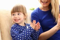 Gioco sveglio della bambina con il picchiettio-un-dolce della mamma fotografie stock