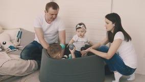 Gioco sveglio della famiglia in stagno delle palle Divertiresi della madre, del padre, del figlio e della figlia archivi video