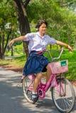 Gioco tailandese della scolara rischioso su una bicicletta, nel parco. Fotografia Stock