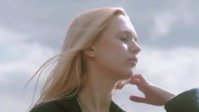 Gioco teenager attraente della ragazza con i suoi capelli biondi archivi video