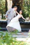 Gioia della sposa e dello sposo contro la fontana del contesto Immagini Stock
