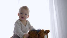 Gioia di emozione del bambino, condimento allegro del neonato che guida sul giocattolo equino nella sala stock footage