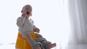 Gioia di emozione di seduta e delle risate sane del ragazzo del bambino su banale nella stanza luminosa video d archivio