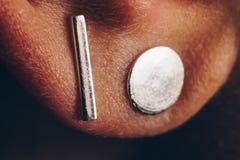 Gioielli d'argento sul primo piano dell'orecchio macro degli orecchini del metallo Minimalismo concettuale lobo della donna bianc fotografie stock libere da diritti