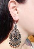Gioielli degli orecchini con i cristalli luminosi in orecchio Fotografie Stock Libere da Diritti