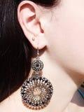Gioielli degli orecchini con i cristalli luminosi in orecchio Immagini Stock Libere da Diritti