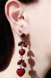 Gioielli degli orecchini con i cristalli luminosi in orecchio Fotografia Stock