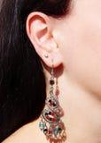 Gioielli degli orecchini con i cristalli luminosi in orecchio Immagini Stock