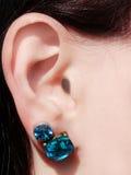 Gioielli degli orecchini con i cristalli luminosi in orecchio Fotografia Stock Libera da Diritti