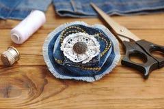 Gioielli del fiore del denim Forbici, filo, ditale, ago, vecchi jeans femminili su un fondo di legno Che cosa da fare con i vecch Fotografie Stock