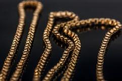 Gioielli del primo piano della catena della collana dell'oro che riflettono sulla tavola di vetro Fotografie Stock Libere da Diritti