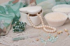 Gioielli delle perle su fondo di tela naturale Mano Fotografia Stock