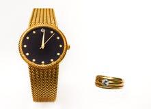 Gioielli dorati dell'anello e dell'orologio isolati su bianco Immagine Stock