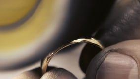Gioielliere che lucida anello dorato stock footage