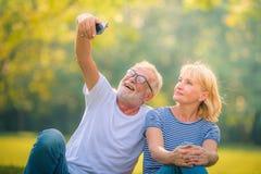 Giornale anziano della lettura delle coppie in giardino al tramonto Amore dell'anziano delle coppie di concetto fotografia stock libera da diritti
