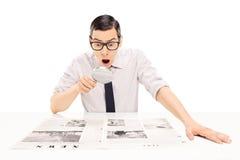 Giornale della lettura dell'uomo con la lente d'ingrandimento Fotografia Stock