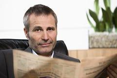 Giornale della lettura dell'uomo d'affari che osserva diritto. Immagine Stock