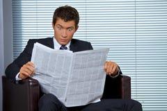 Giornale della lettura dell'uomo d'affari in ufficio Fotografie Stock Libere da Diritti