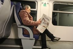 Giornale della lettura dell'uomo nel treno fotografia stock libera da diritti
