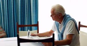 Giornale della lettura dell'uomo senior in camera da letto video d archivio