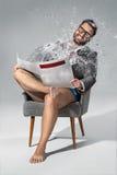 Giornale della lettura dell'uomo su fondo grigio Fotografia Stock Libera da Diritti
