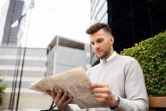 Giornale della lettura dell'uomo sul banco della via della città Fotografie Stock