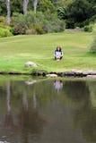 Giornale della lettura della donna che si siede nell'erba fotografia stock libera da diritti