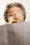 Giornale della lettura della donna con la lente d'ingrandimento Fotografie Stock Libere da Diritti