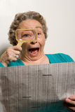 Giornale della lettura della donna con la lente d'ingrandimento Fotografie Stock