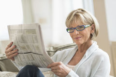 Giornale della lettura della donna mentre rilassandosi sul sofà Immagine Stock