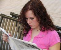 Giornale della lettura della giovane donna fotografia stock