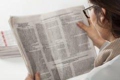 Giornale della lettura della giovane donna Immagini Stock