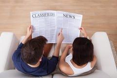 Giornale della lettura delle coppie insieme sul sofà immagine stock